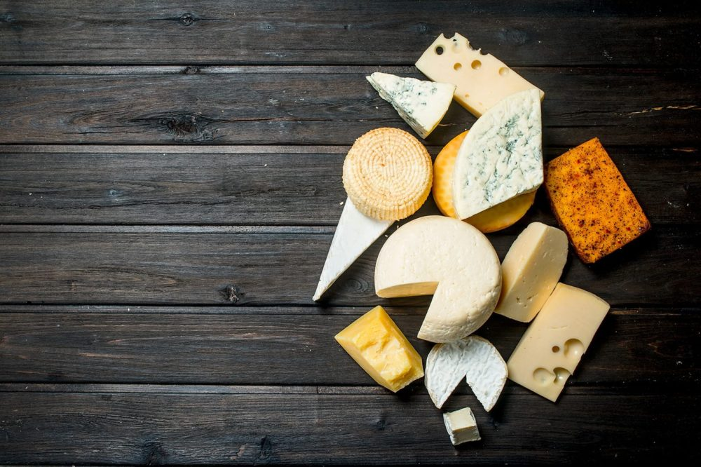 A variety of cheese blocks sitting on top of a dark wooden table.