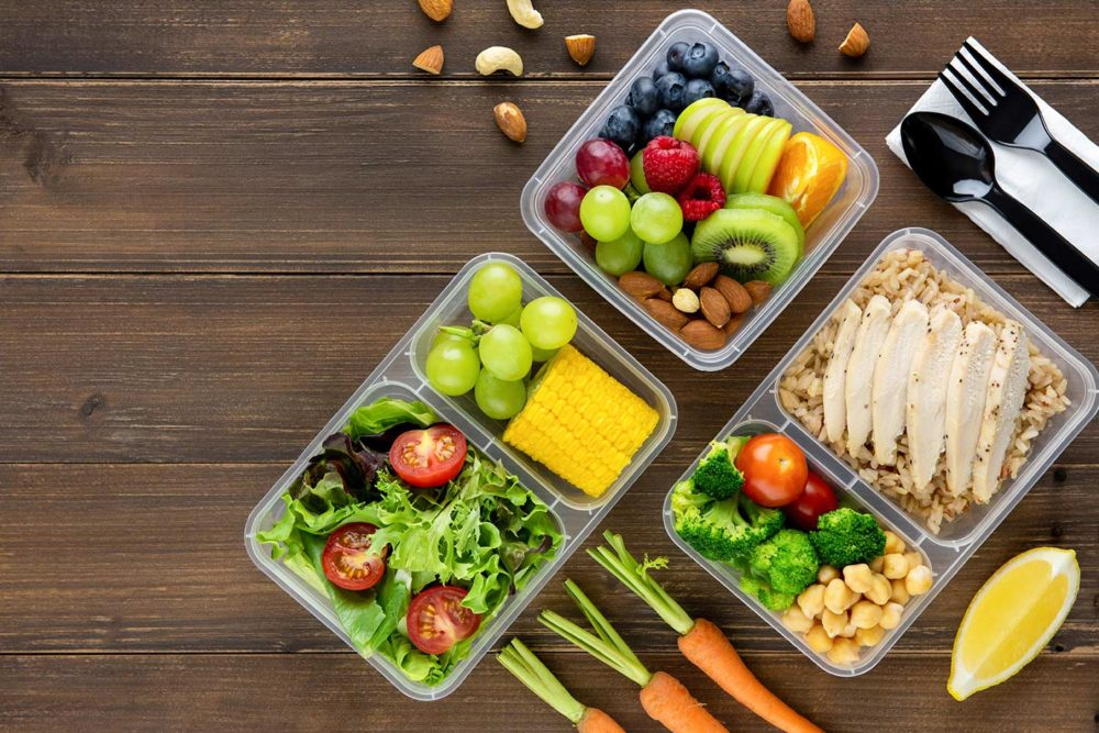 3 separate plastic meal kits with fruit, salad, vegetables, chicken and more inside.