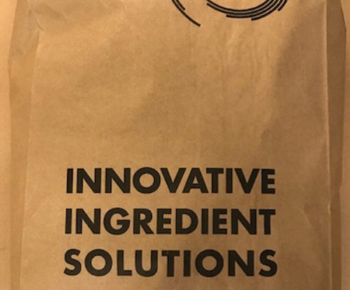 """A brown paper bag, filled with flavoring powder, with the words """"Innovative Ingredient Solutions"""" printed on the front."""