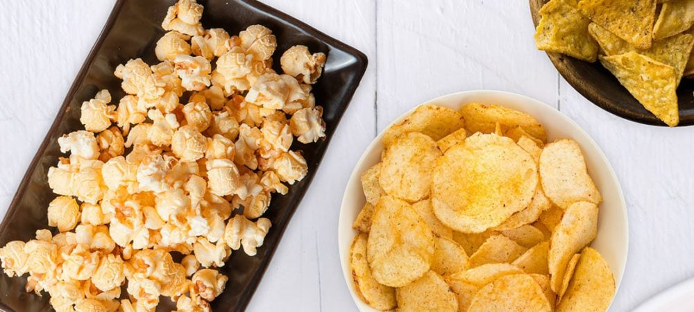 Popcorn sitting on a rectangular plate next to two bowls of seasoned potato chips.